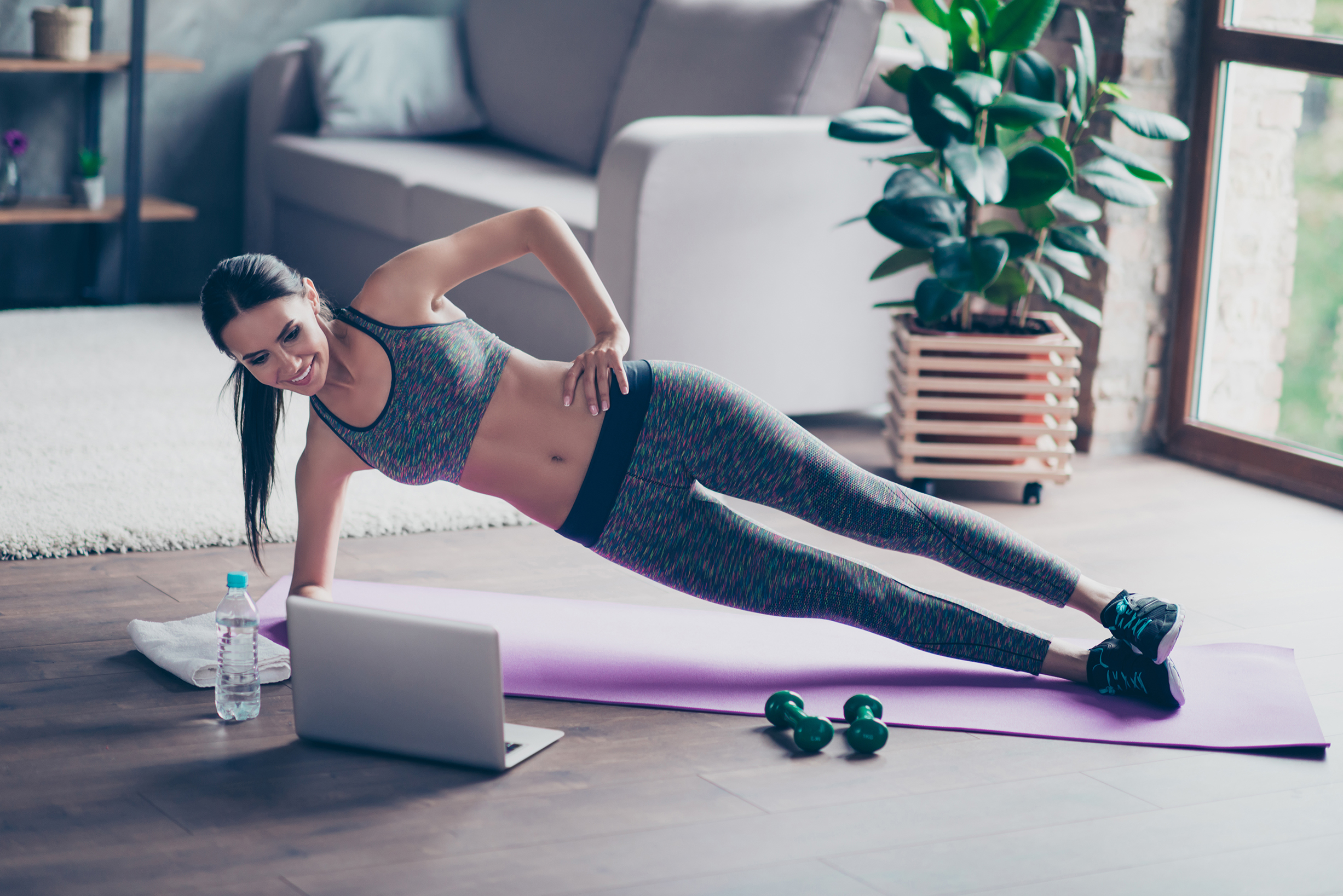 Beautiful sporty cheerful woman is doing side plank exercise. Sh
