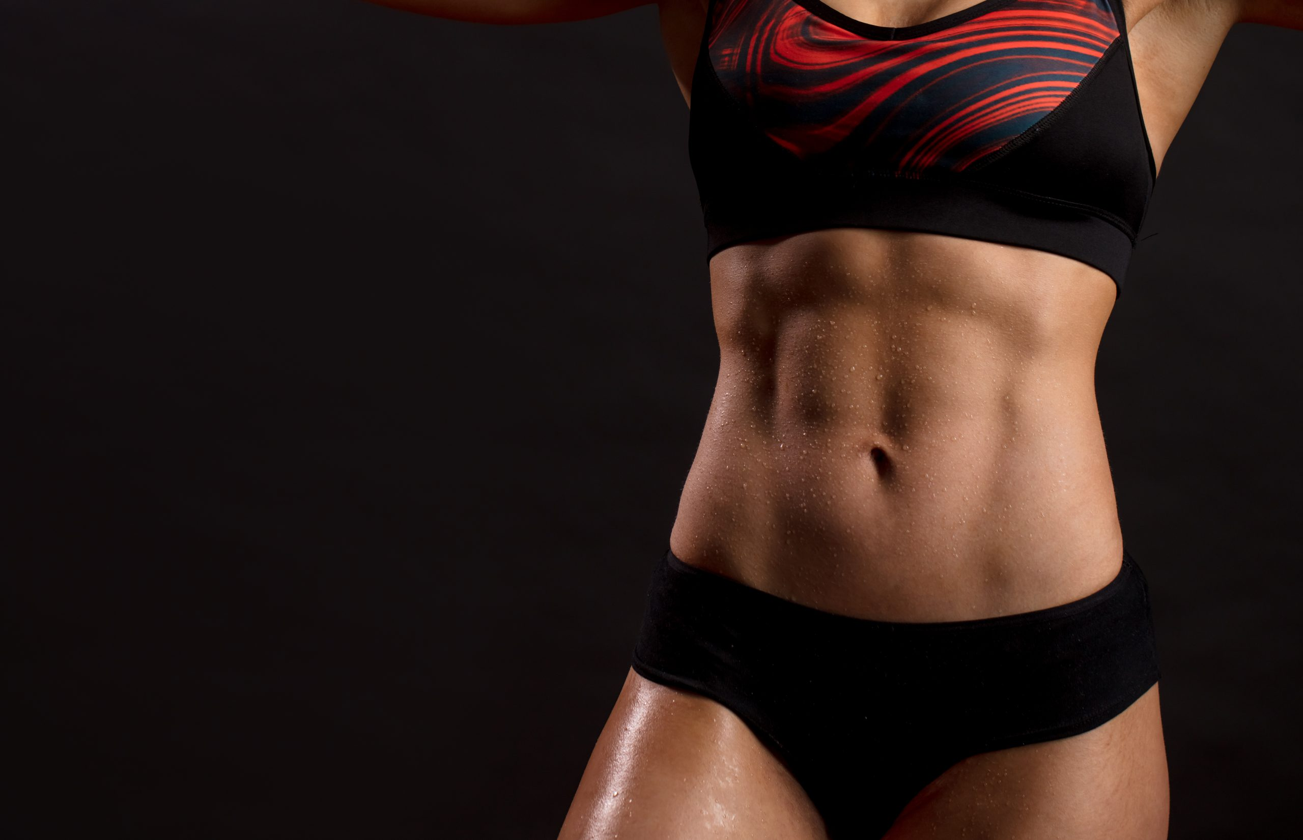 Unrecognizable woman showing off her perfect muscular ripped abs, close up.