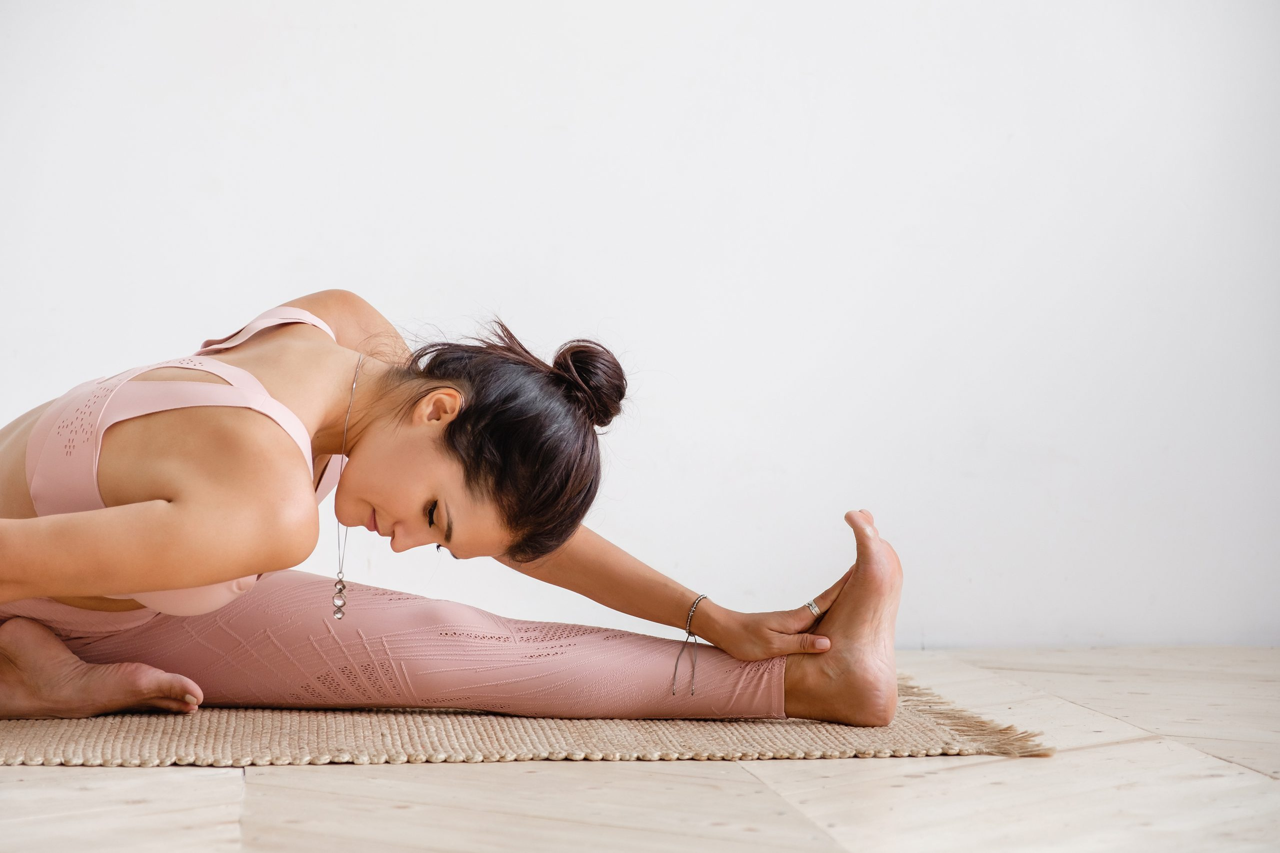 Close-up of a pacified young well-groomed brunette woman doing stretching while doing Pilates exercises sitting on a rug in a pink gymnastic suit on a white background. Place for advertising